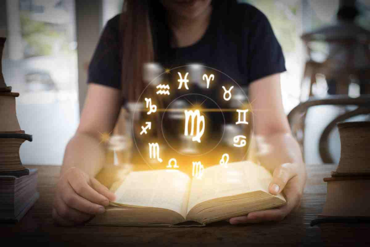 Chica sosteniendo un libro del que sale un círculo con los 12 signos del zodíaco
