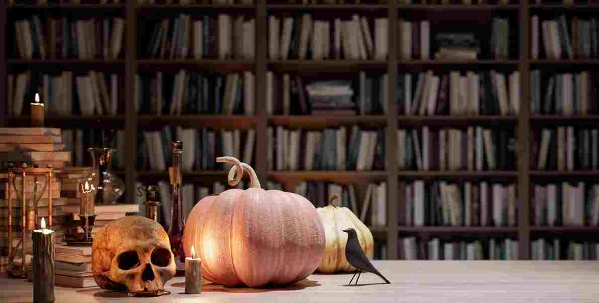 A table with candles, pumpkins and a skull and a library behind it