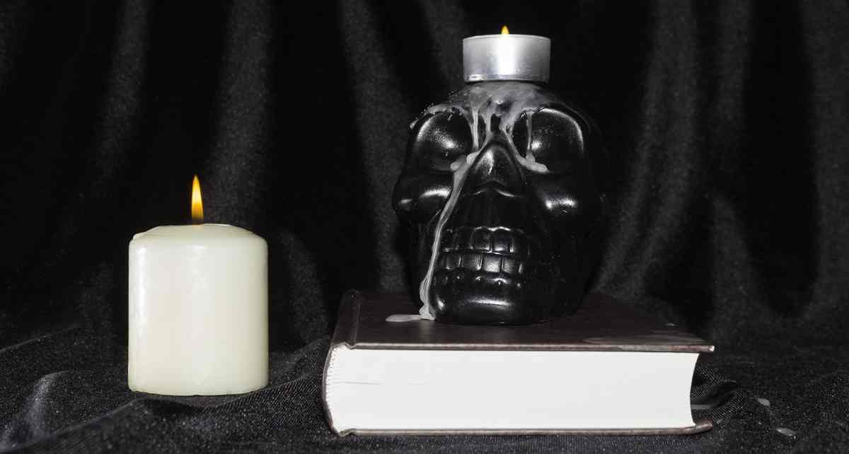 A black skull on a book and with a candle on top of it and next to it