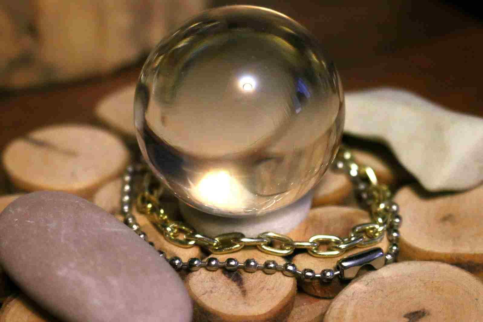 Una bola de cristal rodeada de colgantes y piedras mágicas