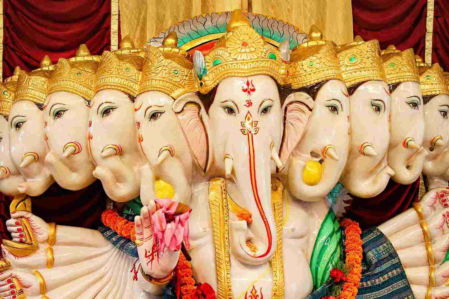 Un dios de la cultura hindú vestido con ropas coloridas, muchas caras y brazos y colgantes de flores