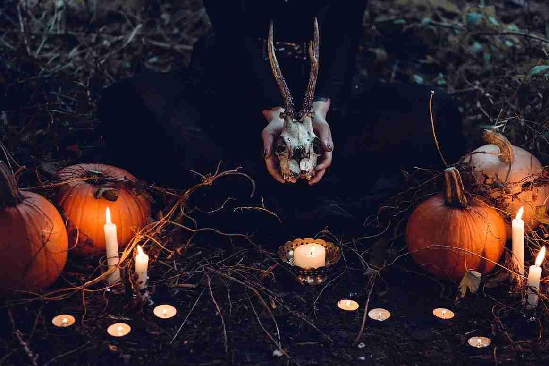 Una bruja con una calavera en la mano rodeada de velas y otros objetos mágicos