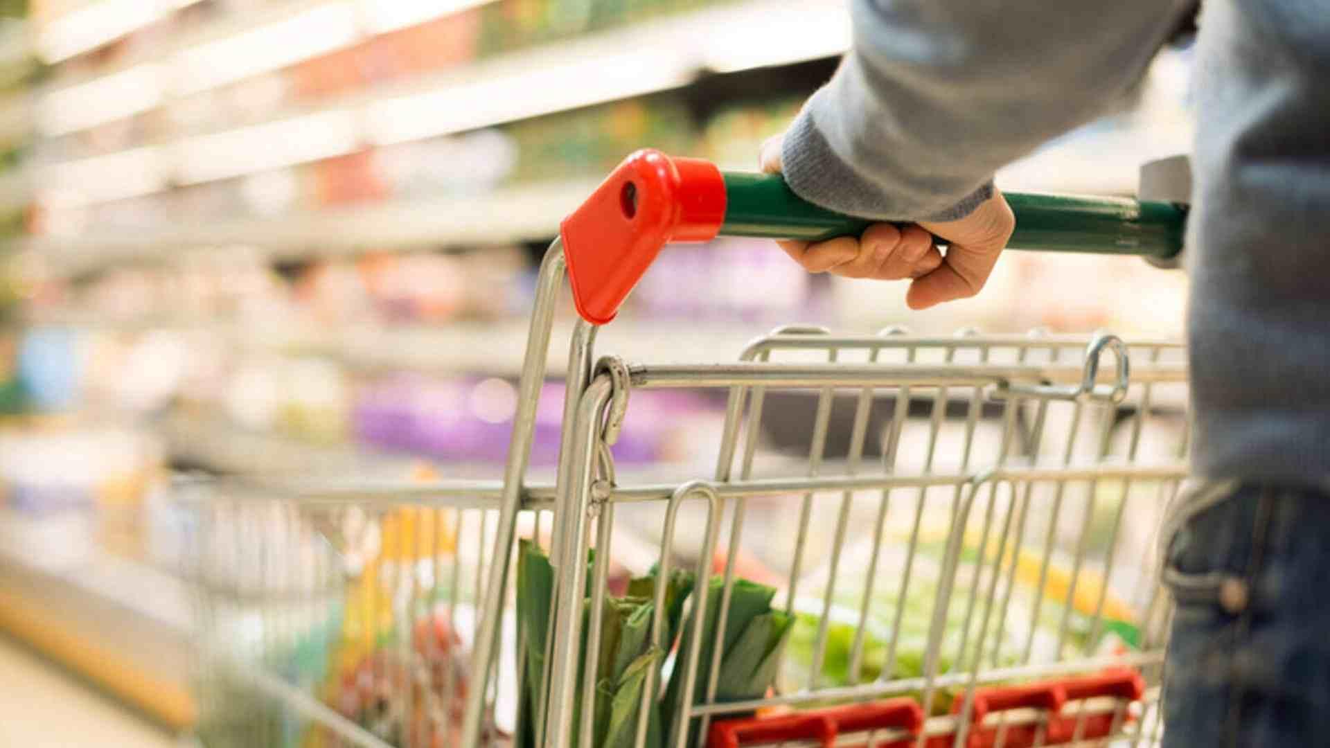 Una persona comprando con un carro de la compra en un supermercado